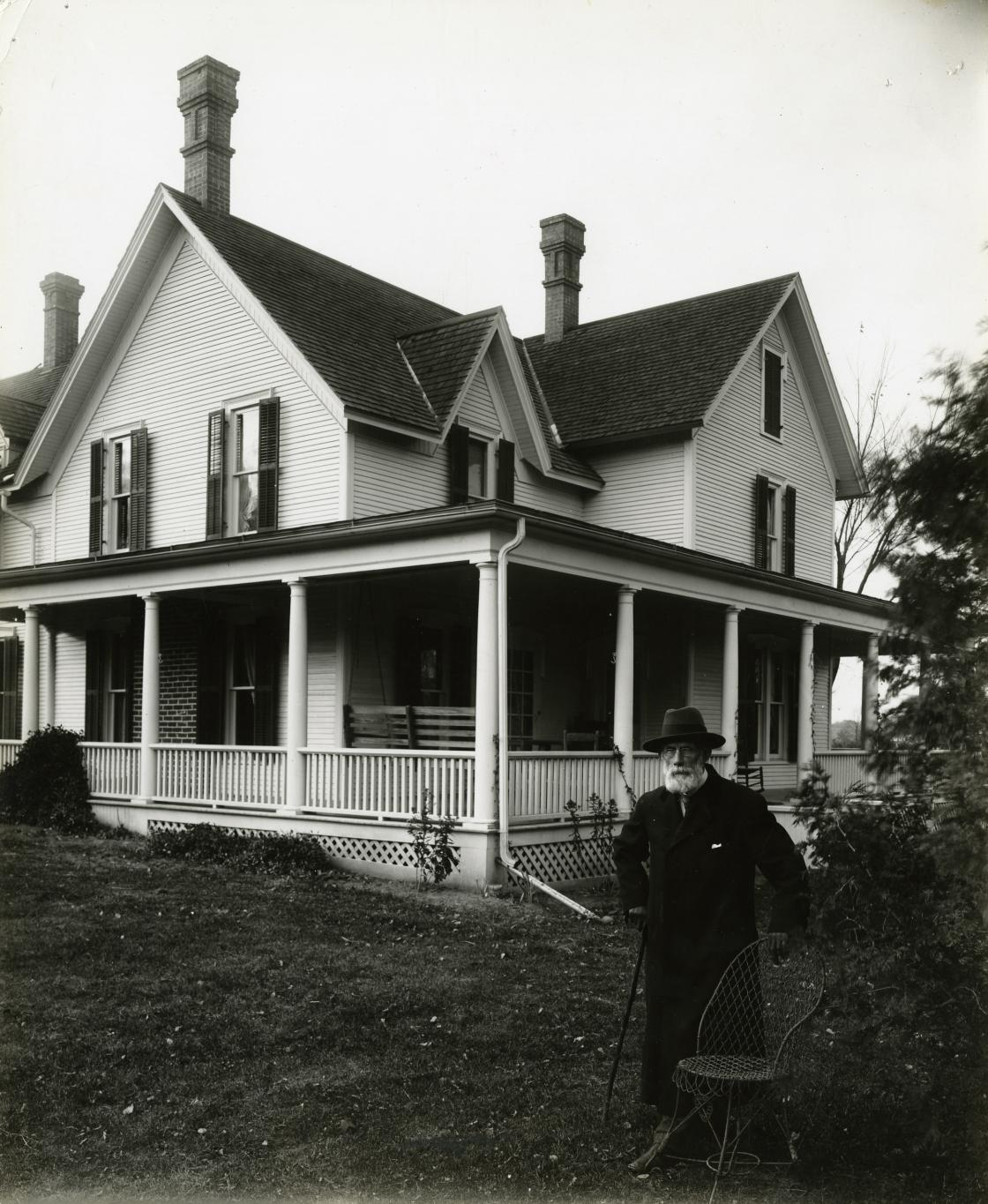 Henry Wood Booth, circa 1912. Photograph Collection of Cranbrook Archives (CC278-1). Henry Booth is standing in the yard of the Cottage at Cranbrook. The view is of the east side of the house, which faced Cranbrook Road.