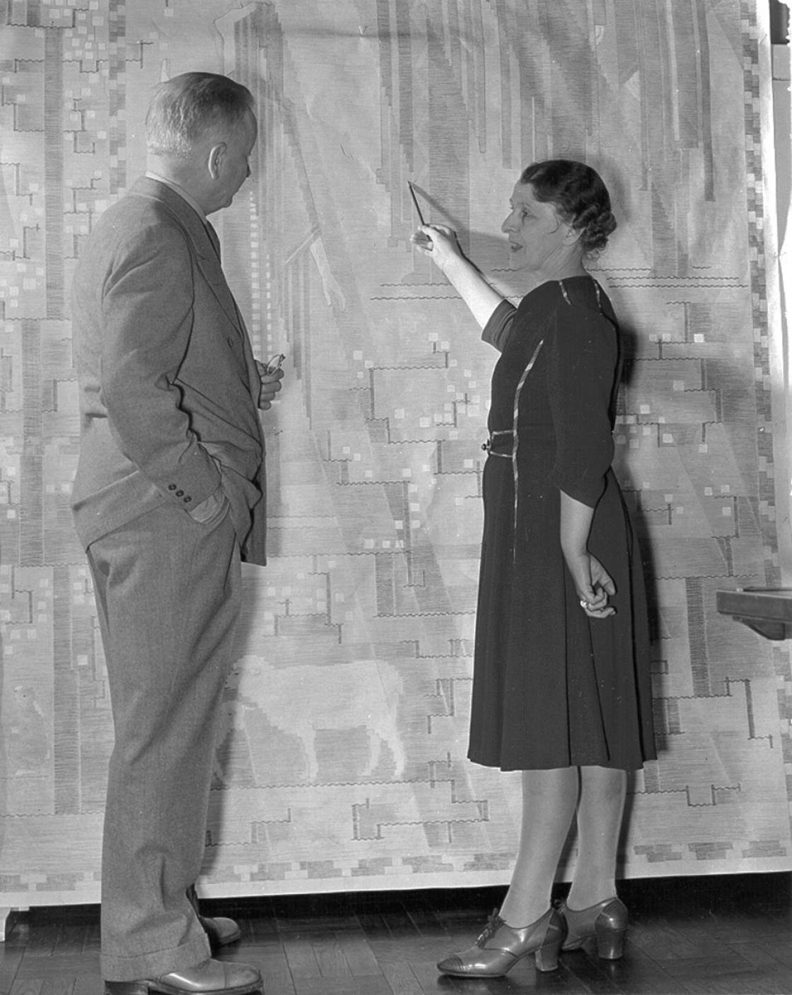 Loja Saarinen showing Eliel Saarinen a cartoon of their tapestry, The Sermon on the Mount, April 1941. Betty Truxell, photographer. Courtesy of Cranbrook Archives.
