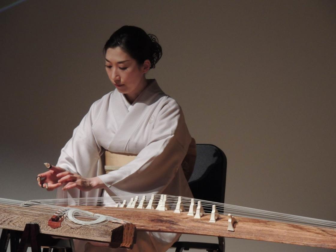 Yuko Asano playing a traditional Japanese stringed instrument, the koto